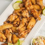 Jerk chicken wings on platter with lime, coleslaw