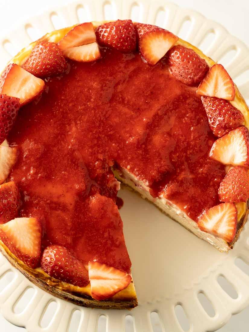keto strawberry cheesecake on a white cake platter