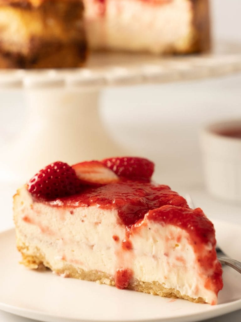 slice of cheesecake with strawberry puree' on white plate with fork