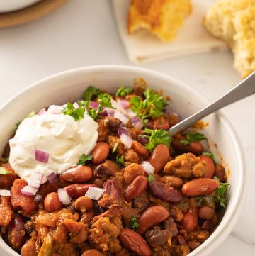 sausage chili with sour cream, onion, parsley in white bowl with corn muffin