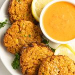 Air fryer crab cakes with lemons, sauce on white plate