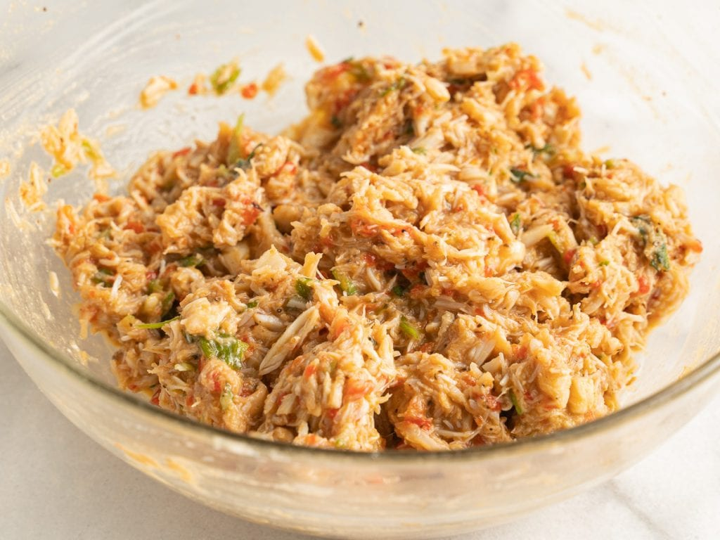 lump crabmeat and seasonings in glass bowl