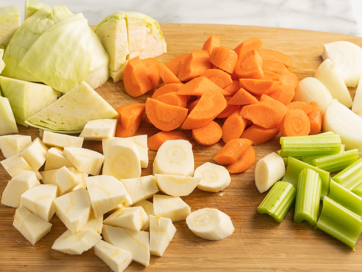 cabbage, carrots, parsnip, celery, onion on cutting board