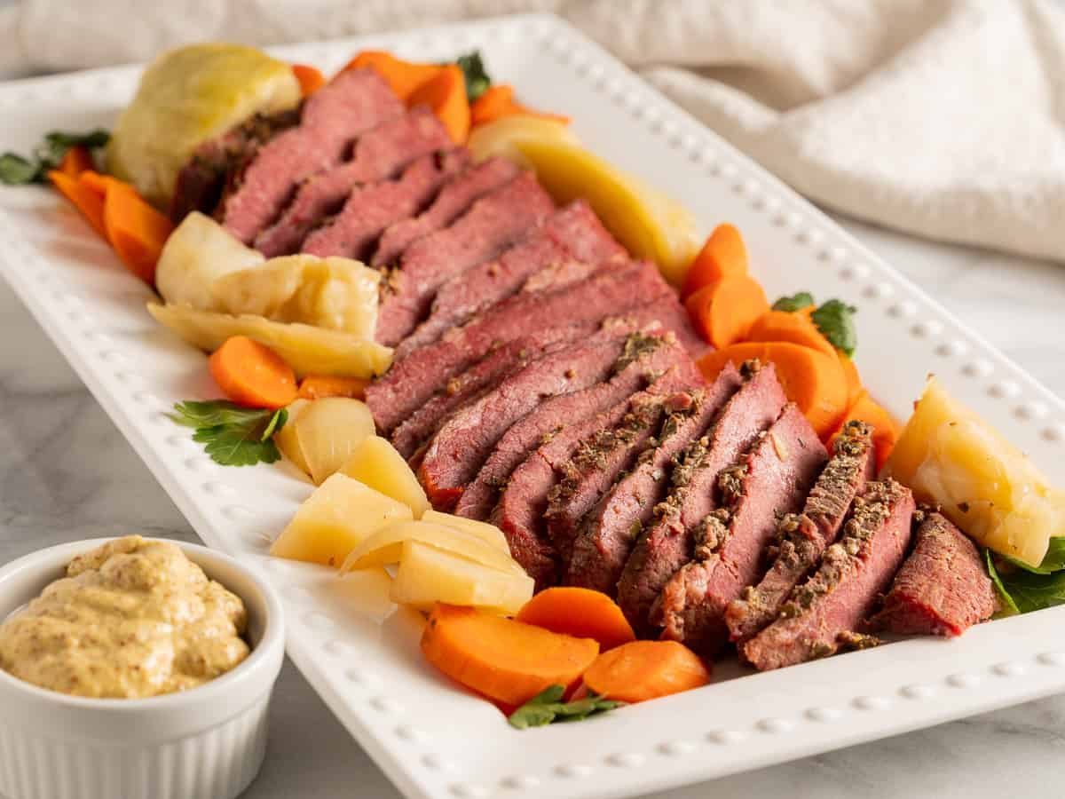 dutch oven corned beef with carrots, cabbage, parsnips on white platter
