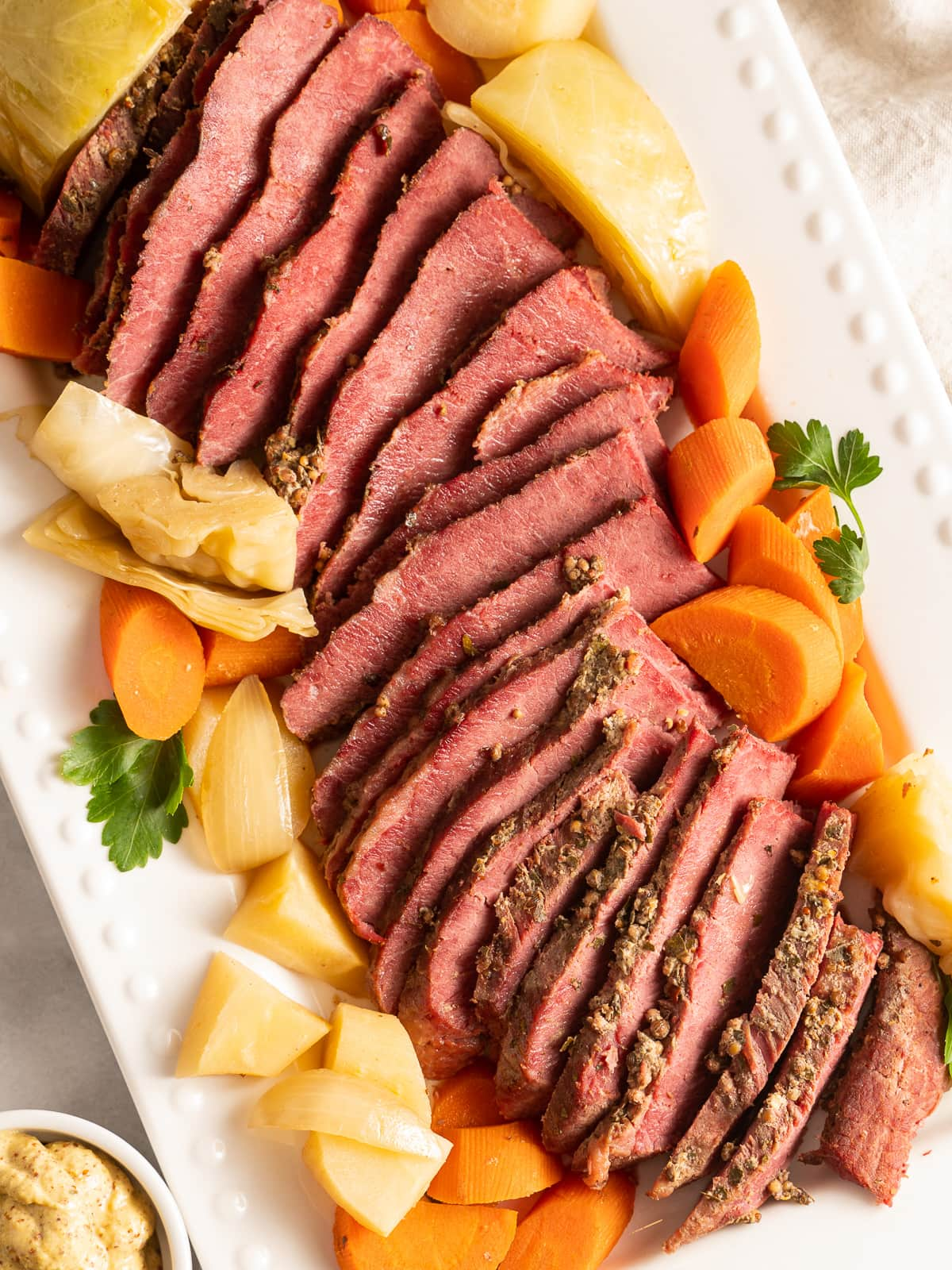 Sliced corned beef, cabbage, carrots, parsnip, onion, celery on white platter