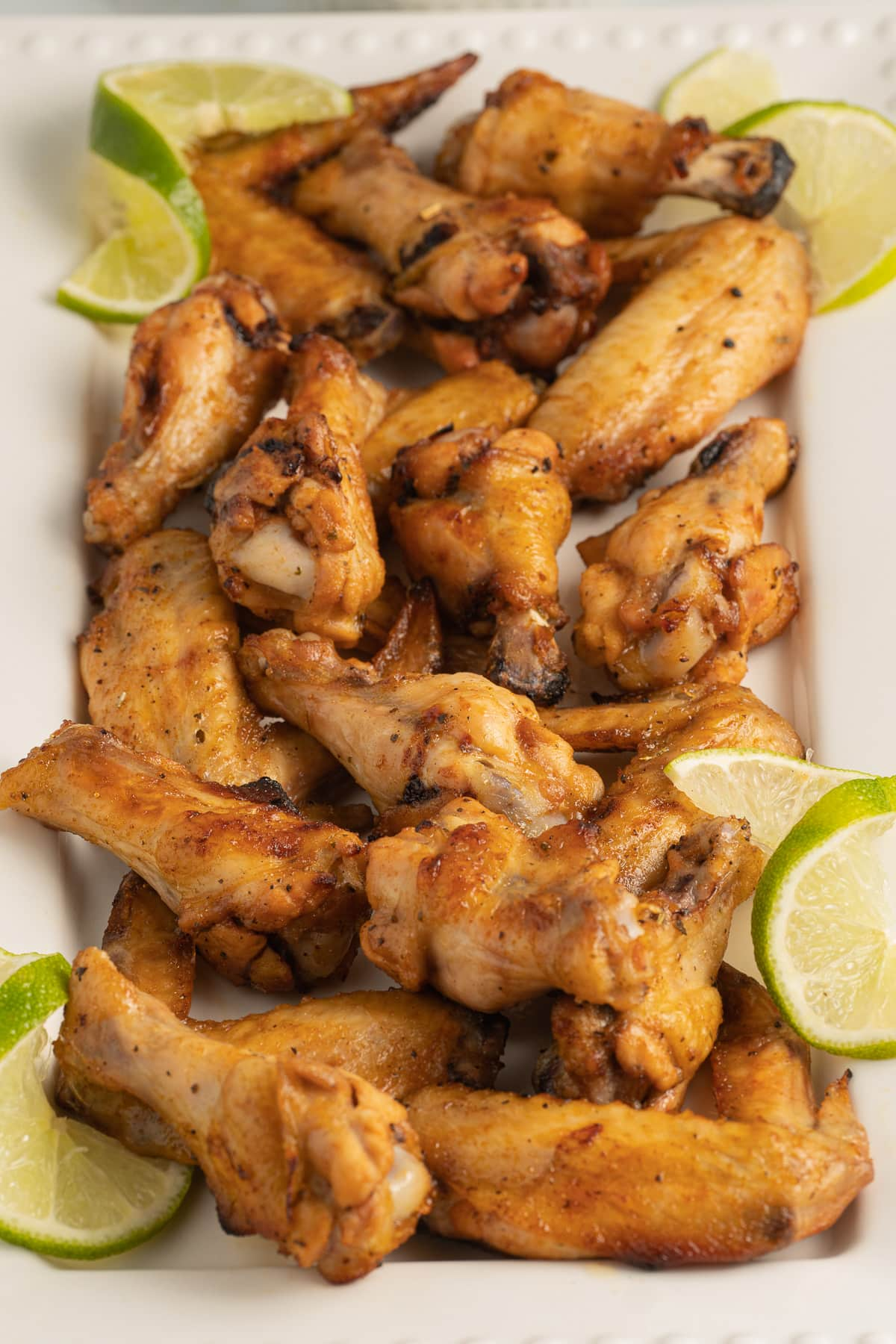 jerk chicken wings on platter with lime