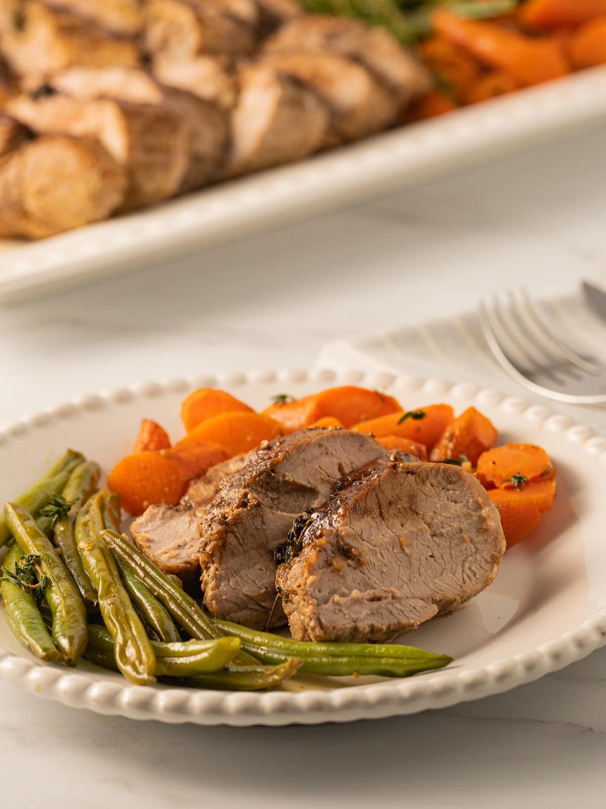 keto pork tenderloin on white plate with carrots and string beans