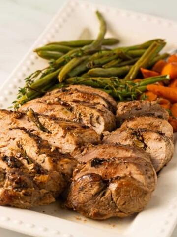 keto pork tenderloin on white platter with carrots string beans