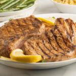 lemon pepper pork chops on white platter and string beans in white bowl