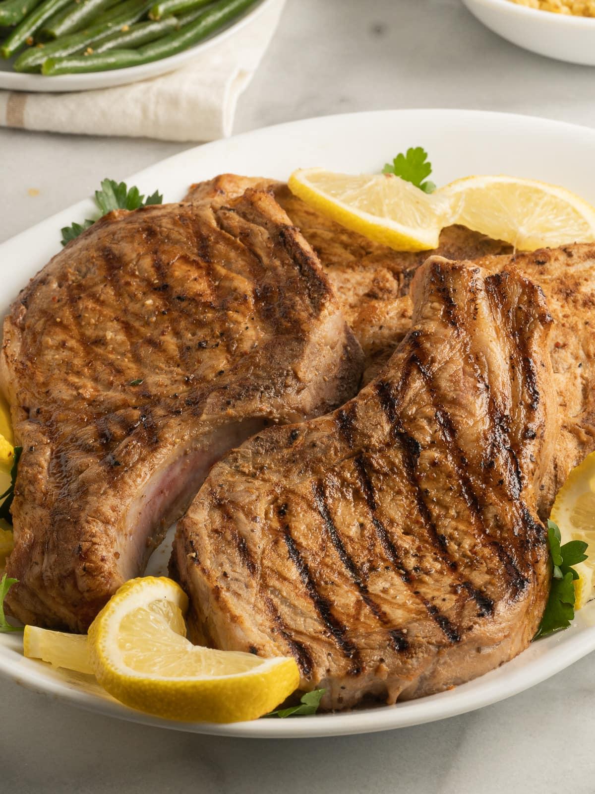 lemon pepper pork chops on whit platter with lemon