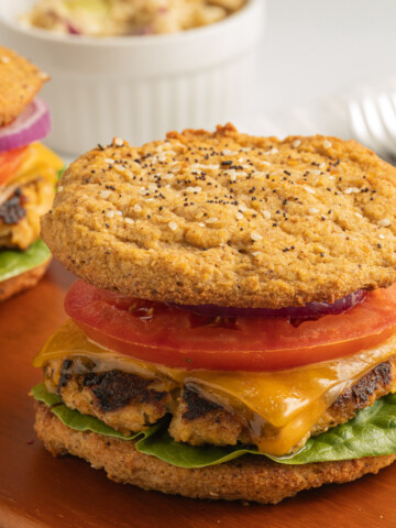 Turkey burger with lettuce, tomato, onion, cheese on bun served on board