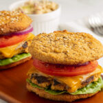 turkey burgers on a roll with cheese, lettuce, tomato, onion on board