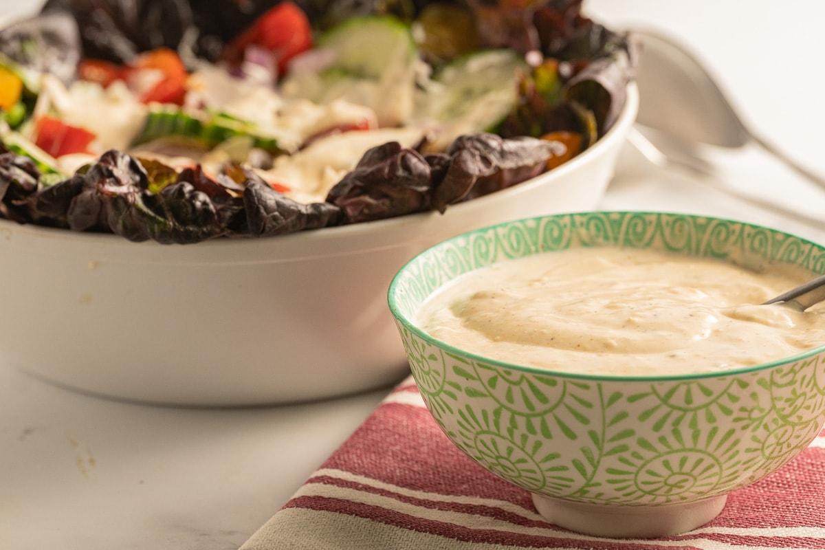 garlic dressing in green bowl, red leaf salad in white bowl