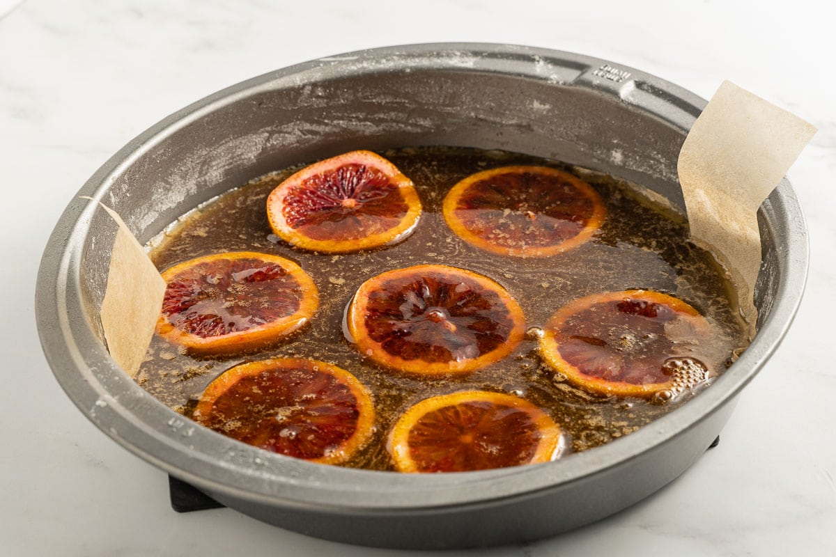 slices of blood orange in brown sugar syrup in cake pan
