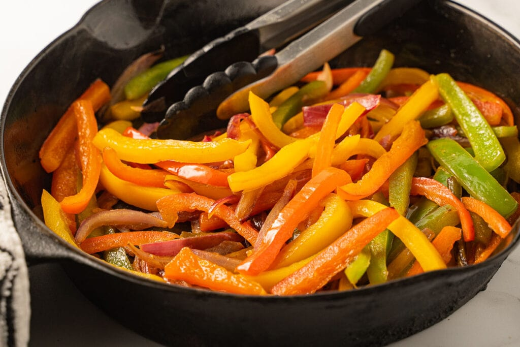 sliced red, yellow, green peppers and onions in cast iron skillet