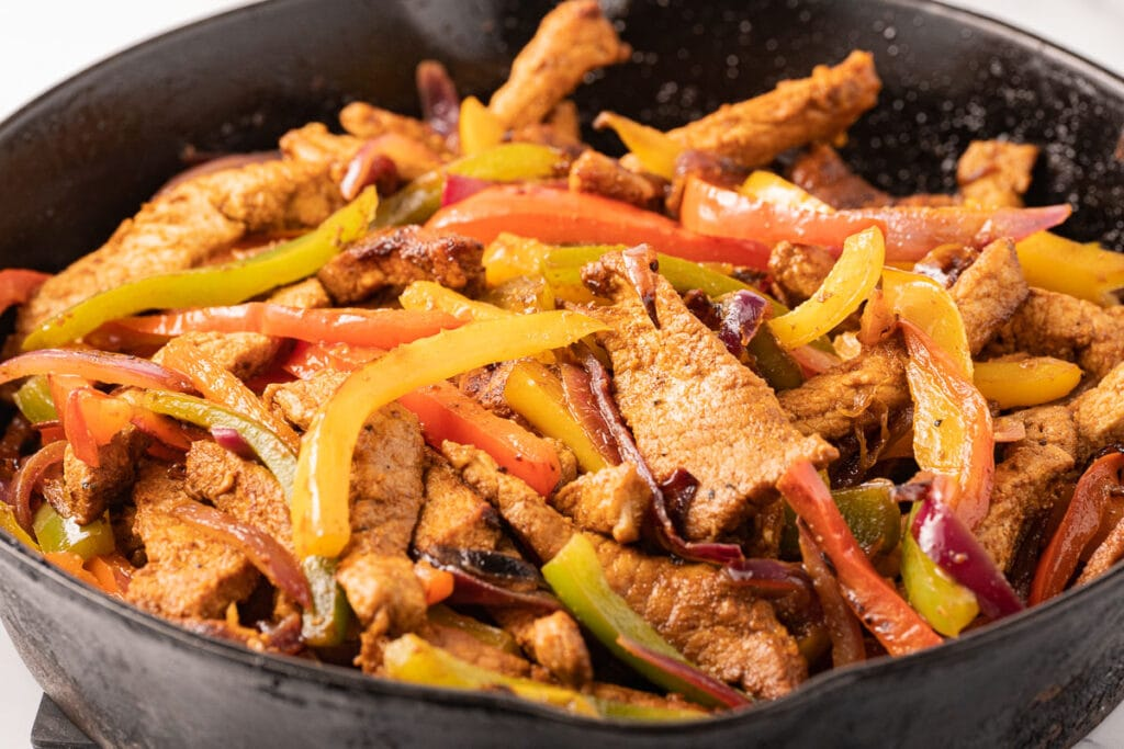 pork slices, green, yellow, red peppers onions sautéed in cast iron skillet