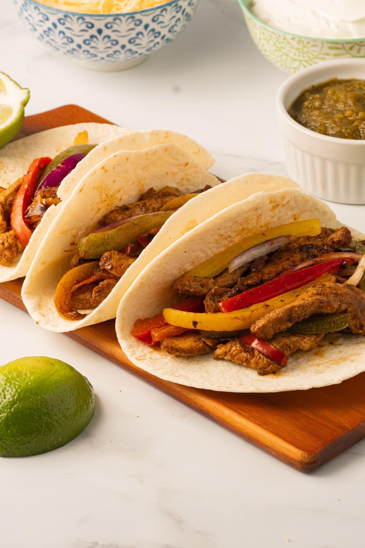 sliced pork, bell peppers in tortilla on board