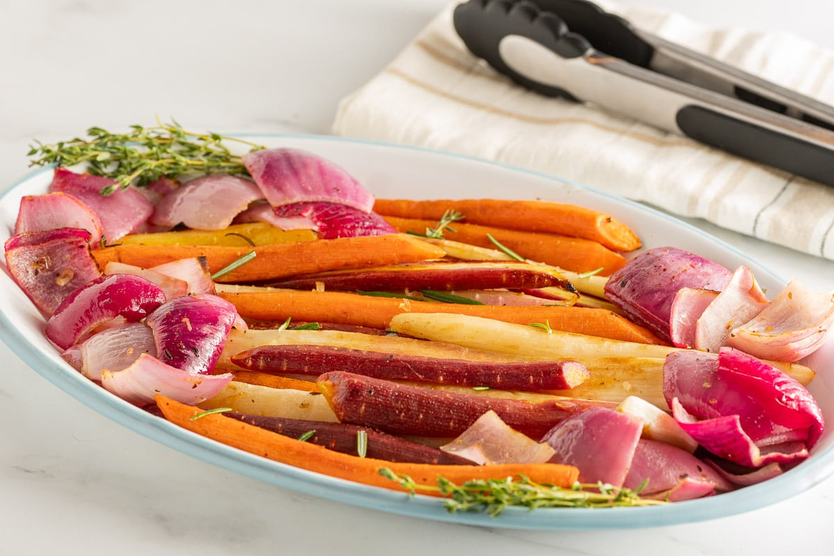 rainbow carrots and red onions on white platter