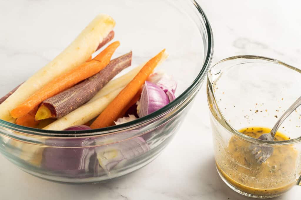 sliced carrots and red onion in glass bowl with cup of marinade