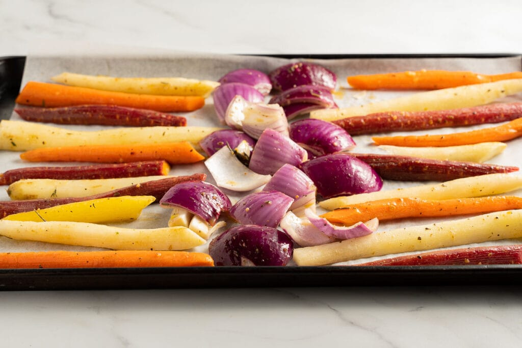 sliced carrots and onions on a baking sheet