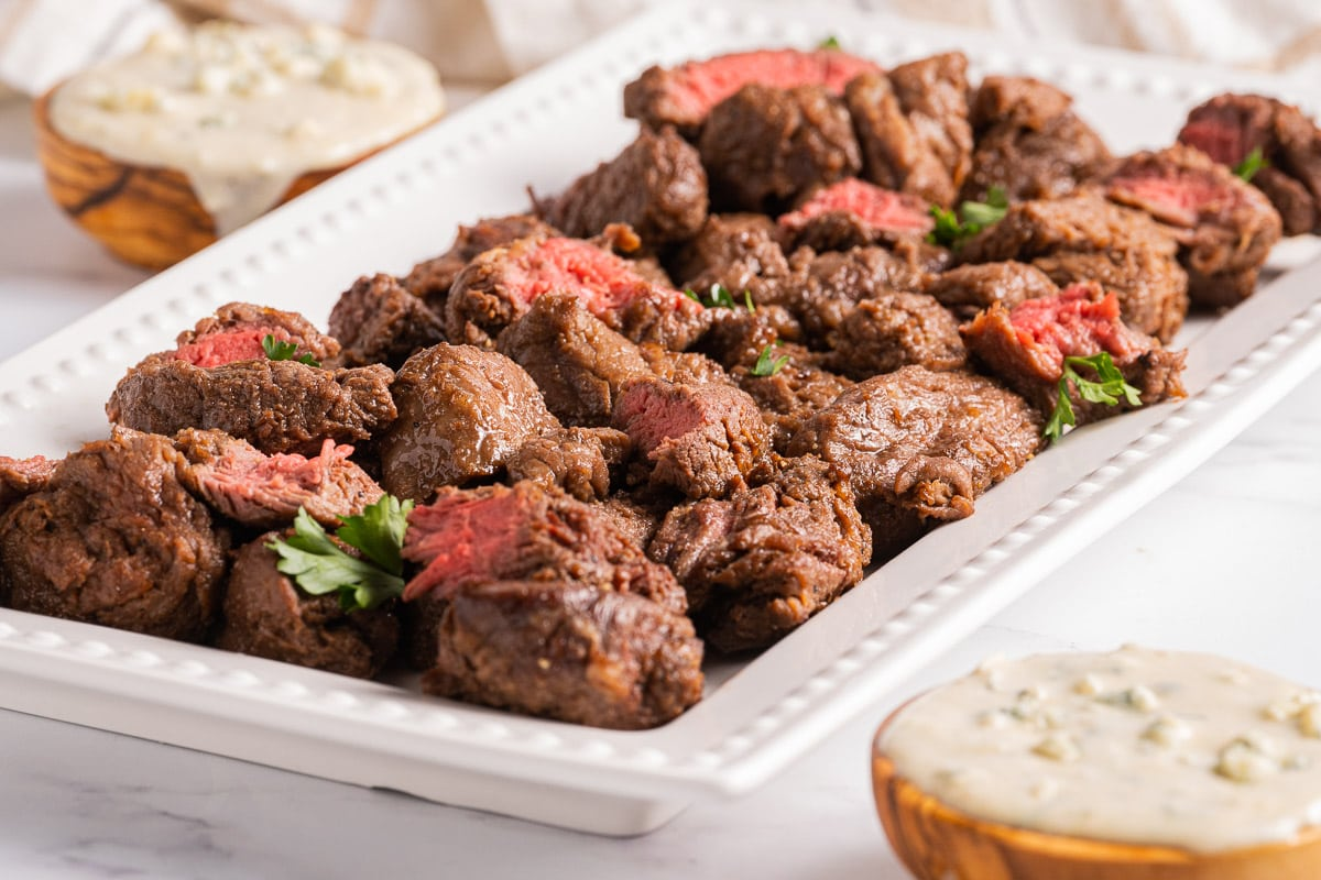 steak bites on platter with blue cheesing sauce in a cup