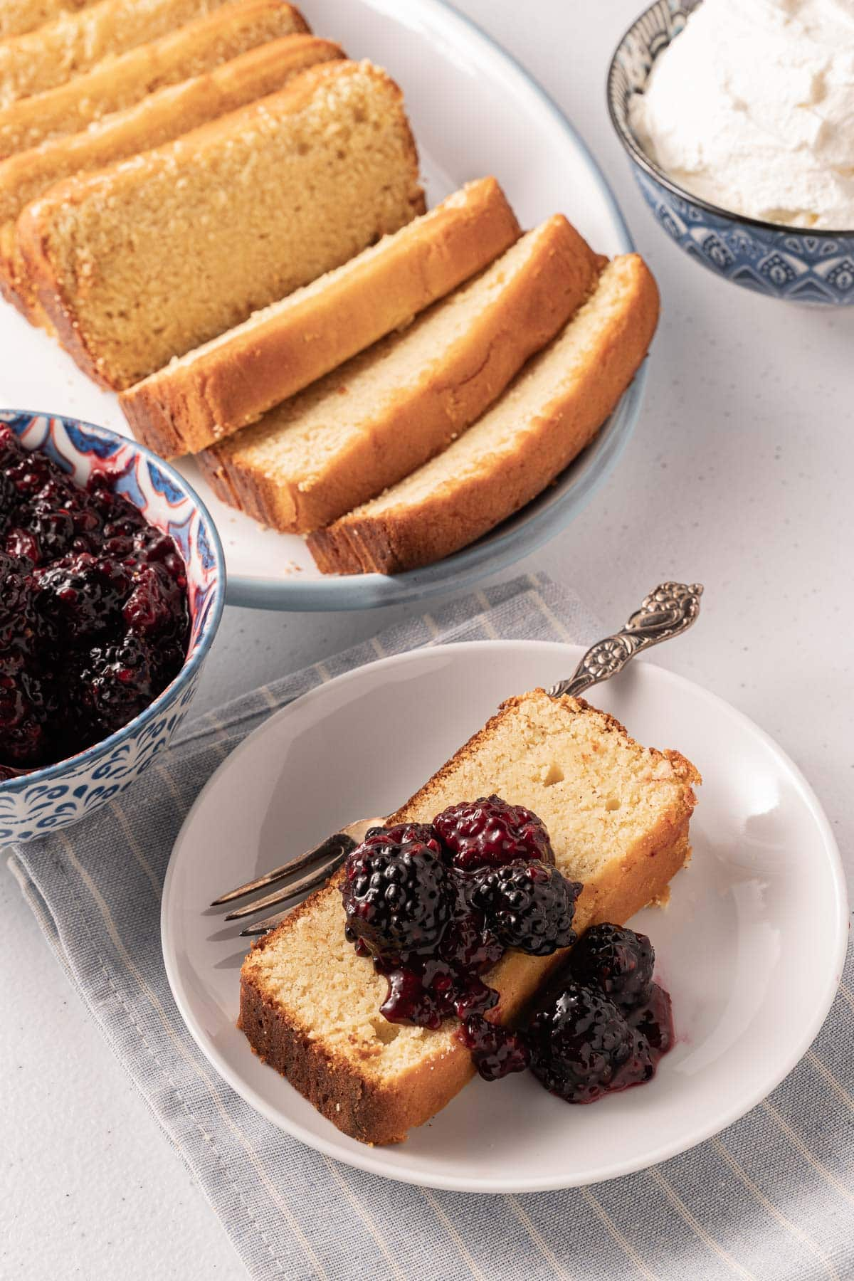 poundcake with blueberry compote on plate, whipped cream