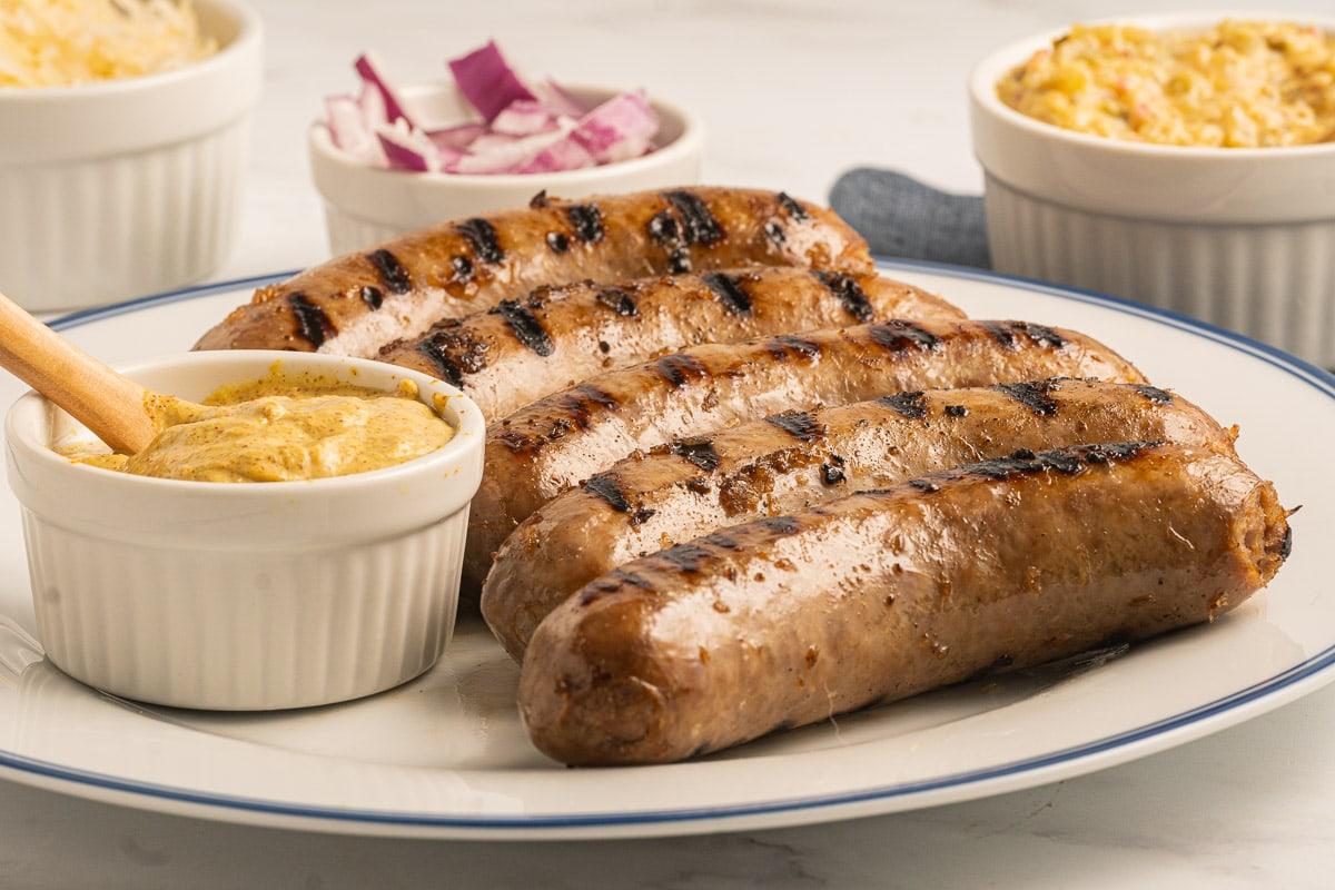 bratwurst on plate with mustard, onions, relish