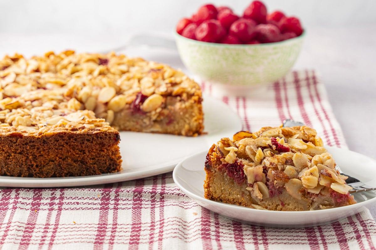 almond cherry cake on platter, bowl of cherries