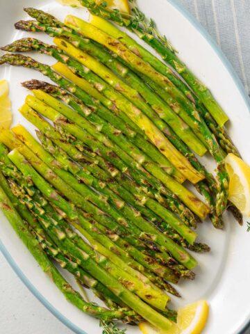 asparagus and lemon on white platter