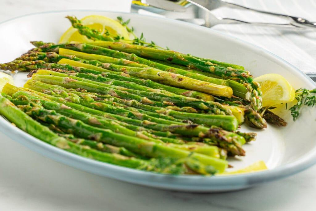 asparagus, lemon on white platter