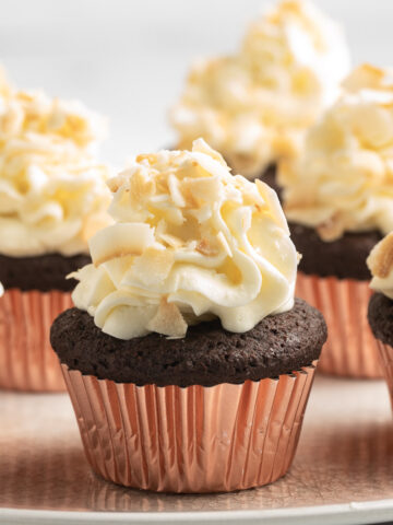 chocolate cupcakes with coconut frosting on plate
