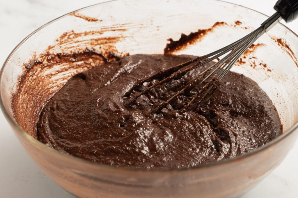 chocolate batter for cupcakes in glass bowl with whisk