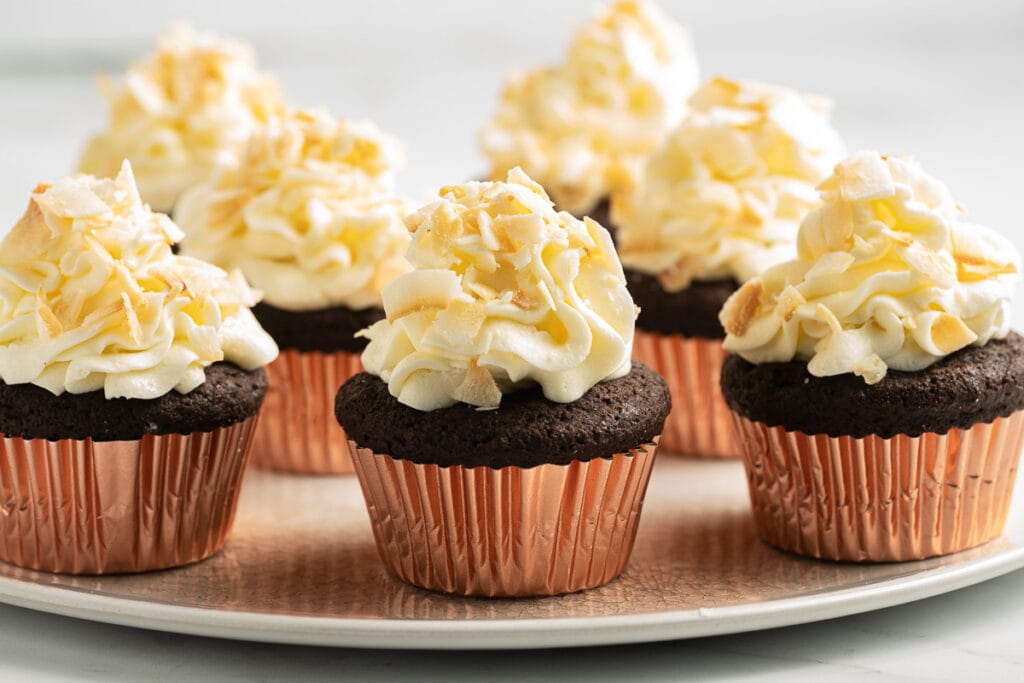 chocolate cupcake with coconut frosting on  white plate