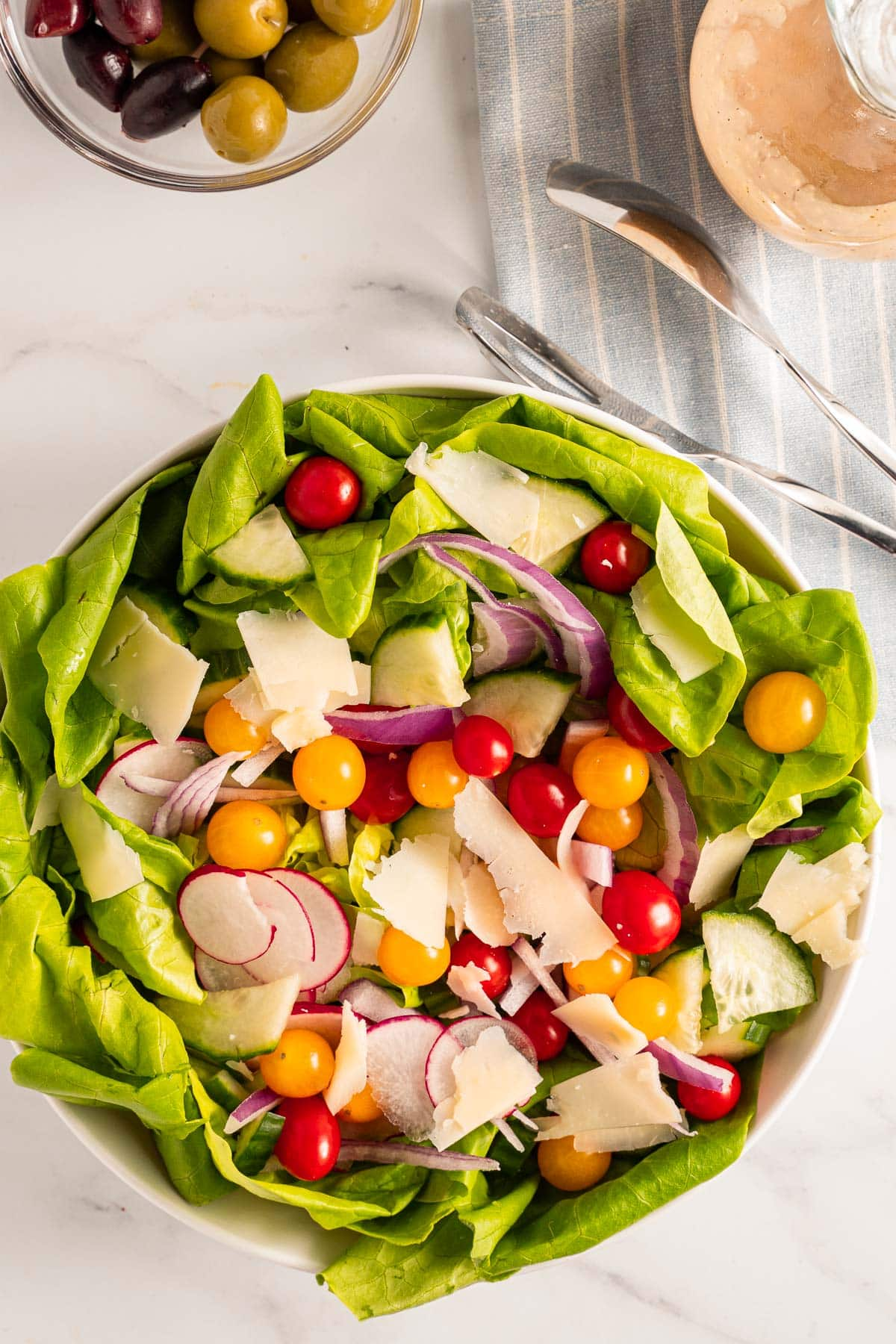 butter lettuce salad with cherry tomatoes, cucumbers, radishes, red onion, cheese in white bowl. with olives and balsamic dressing
