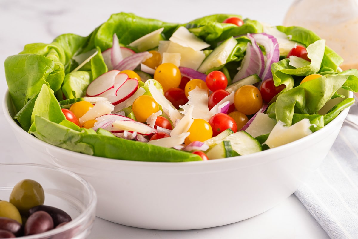 Salad with cherry tomatoes, onions, radishes, cucumbers in white bowl