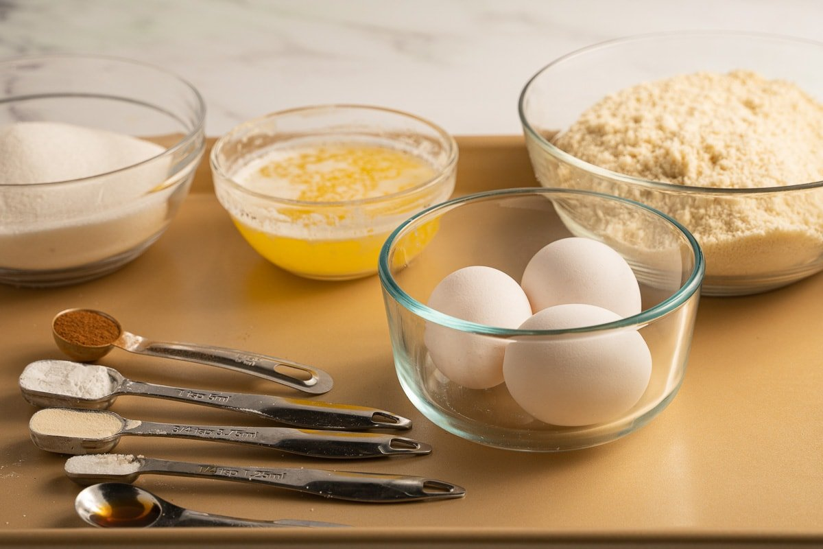 almond, coconut flour, eggs, melted butter, sugar substitute in glass bowl, teaspoons of spices