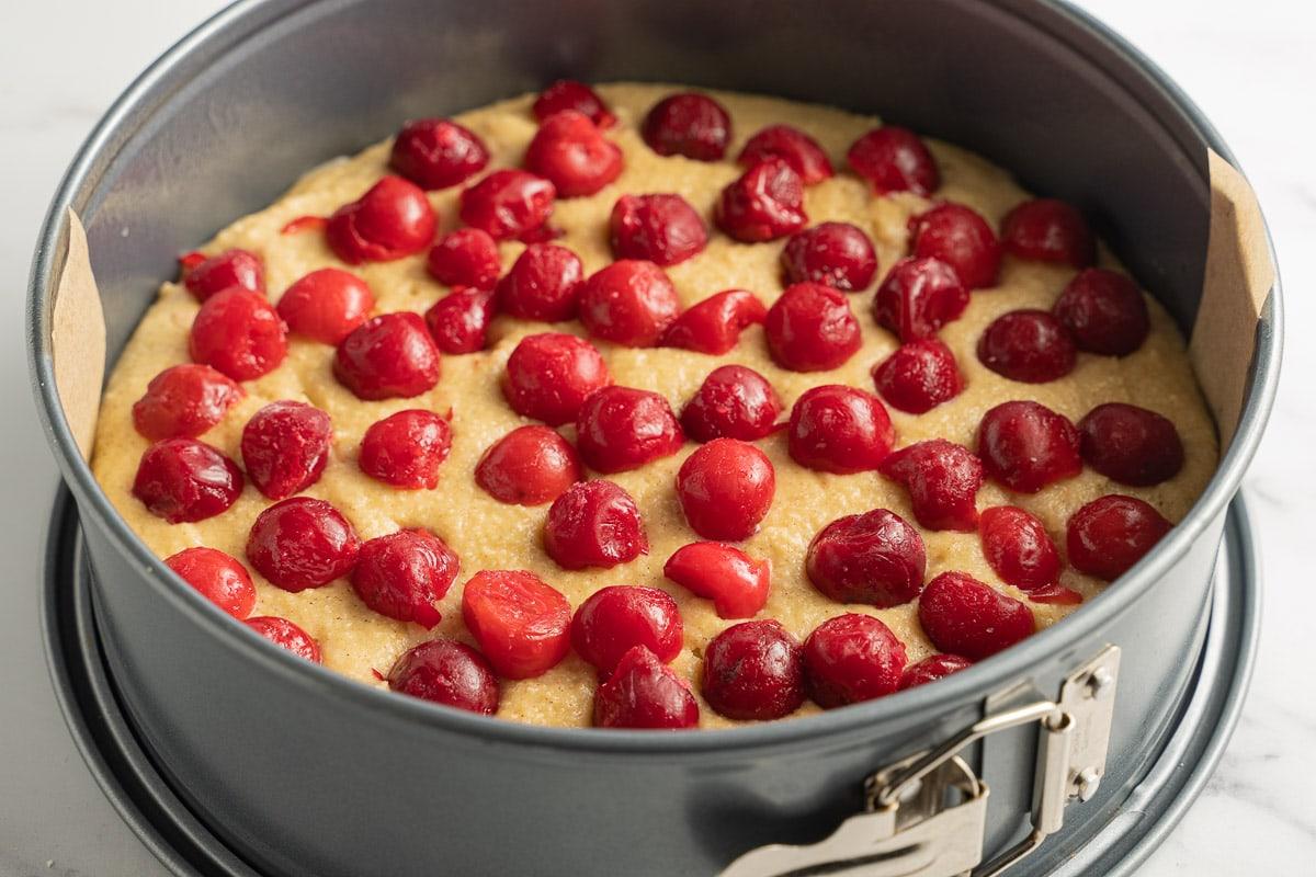 cherries on cake batter in pan