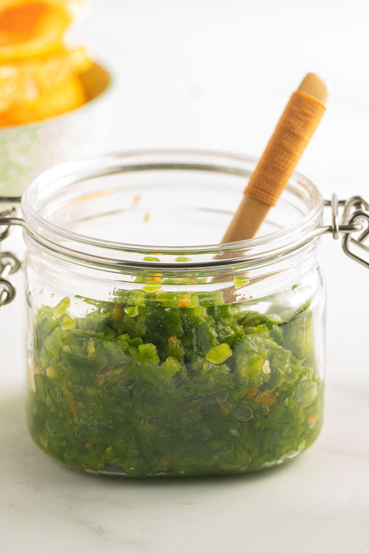 Jalapeno orange relish in glass jar with mini spoon