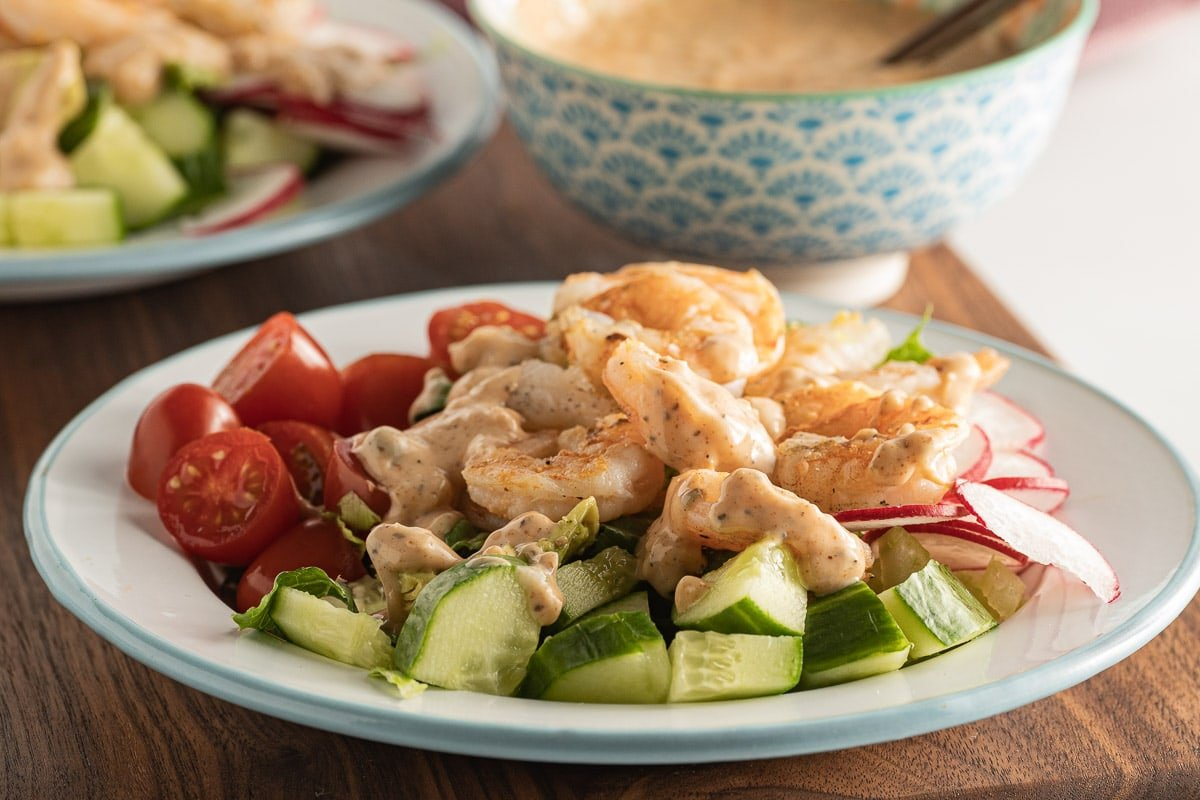 shrimp salad on white plate with dressing in bowl