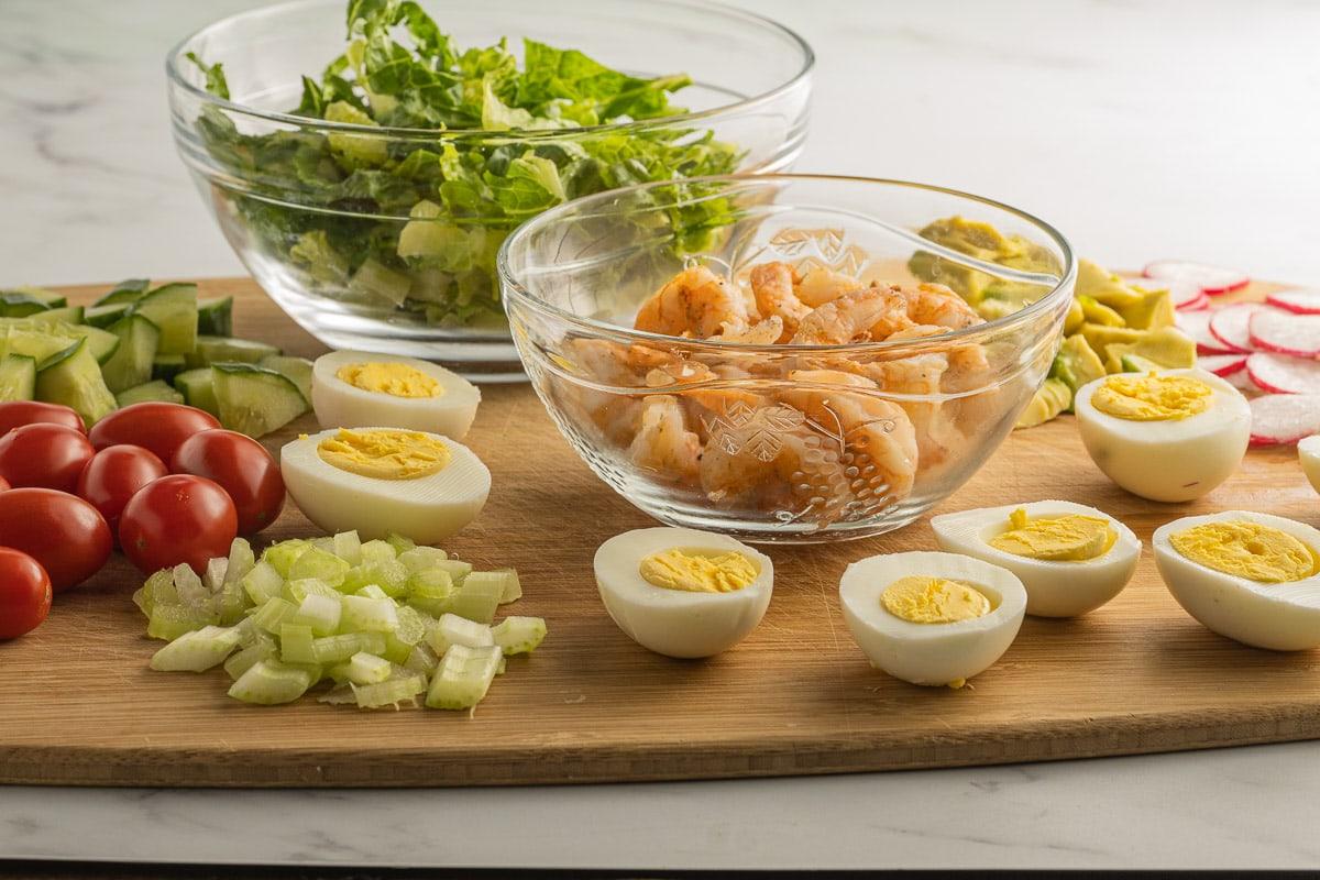 lettuce, grilled shrimp, hard boiled eggs, cucumber, radishes, avocado, tomato on cutting board