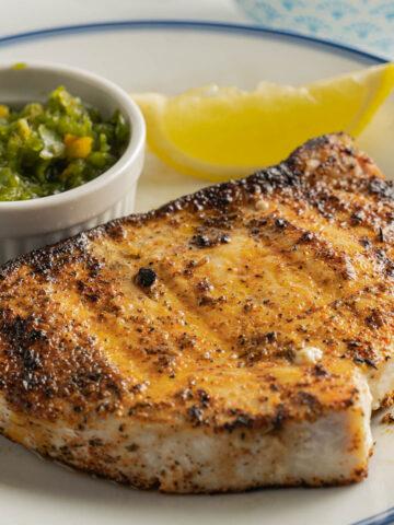 Swordfish on plate with relish and lemon