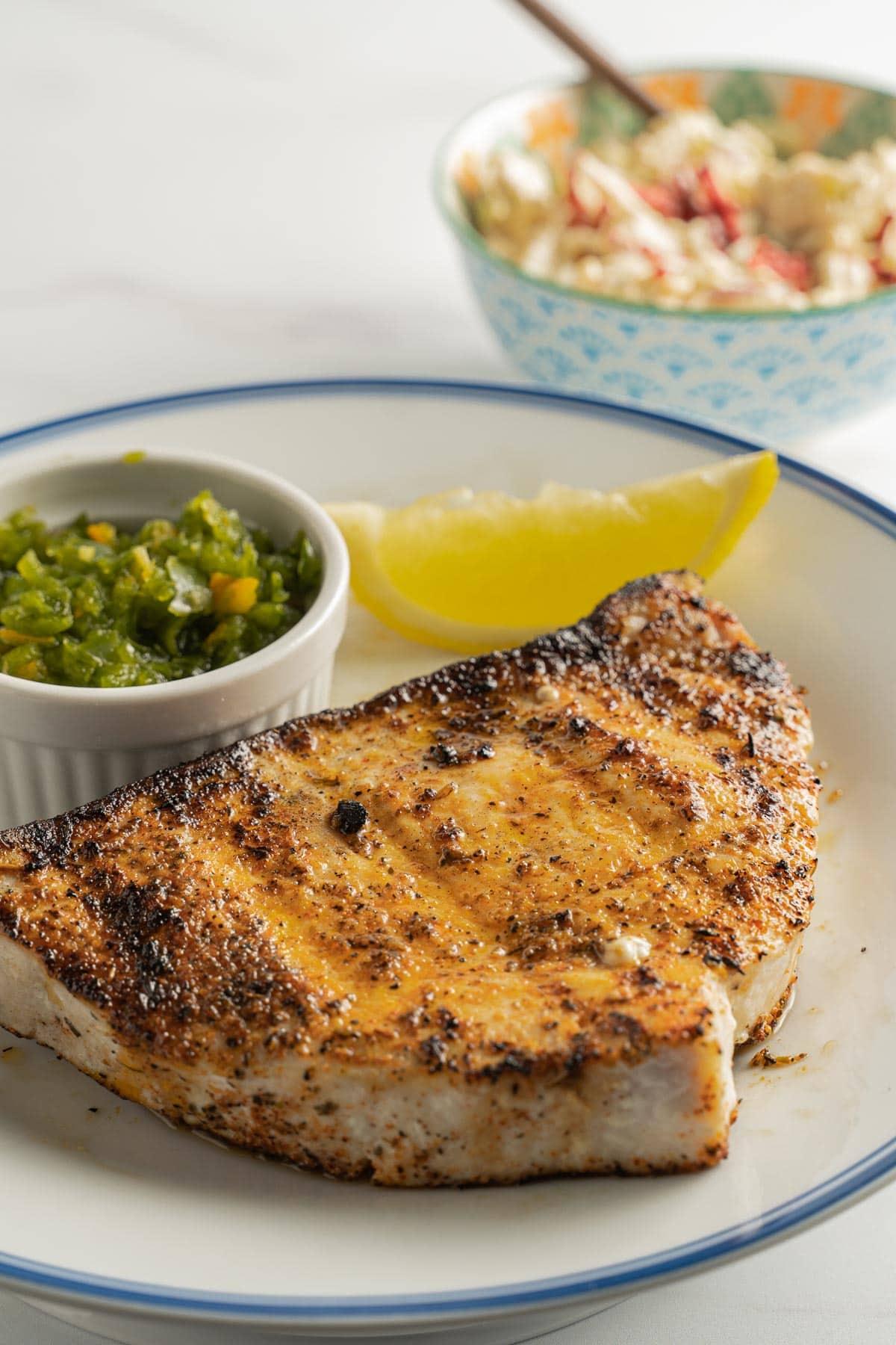 Blackened swordfish on plate with relish and lemon