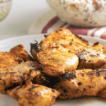 grilled chicken thighs on plate, coleslaw in glass bowl