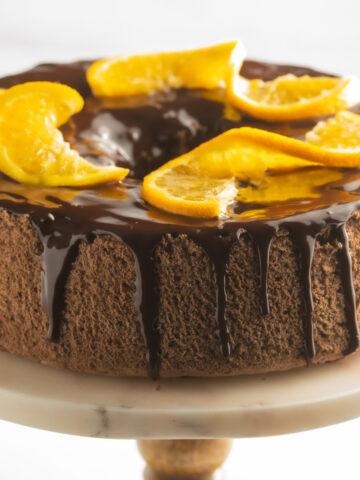 keto chocolate angel food cake with orange slice on cake stand