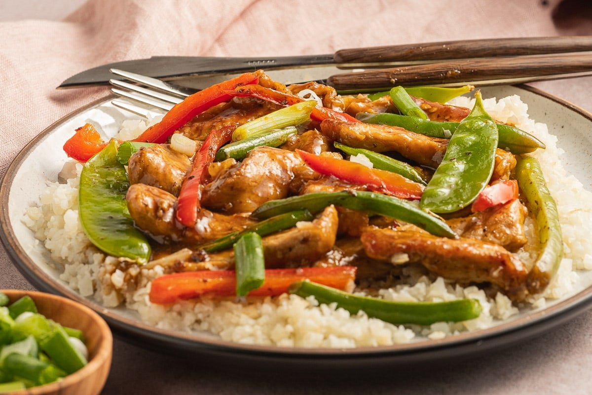 stir fry pork, pepper strips, string beans, cauliflower rice on beige plate, and bowl of chopped scallions.