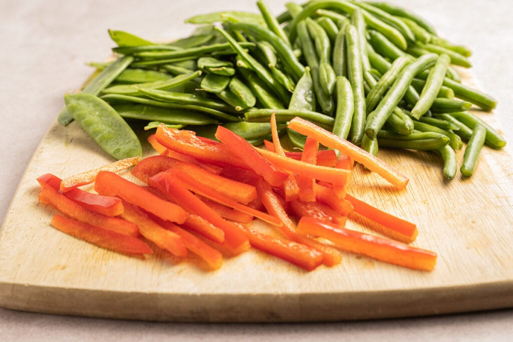 strips of red pepper, string beans, pea pods on cutting board