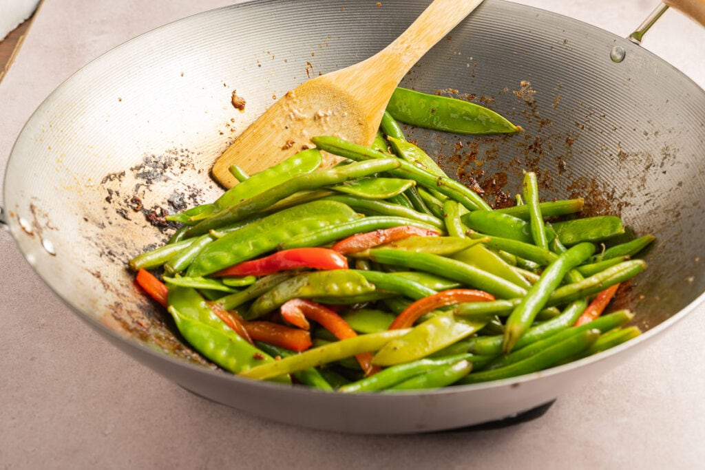green beans, pea pods, red pepper strips in a wok with wooden spoon