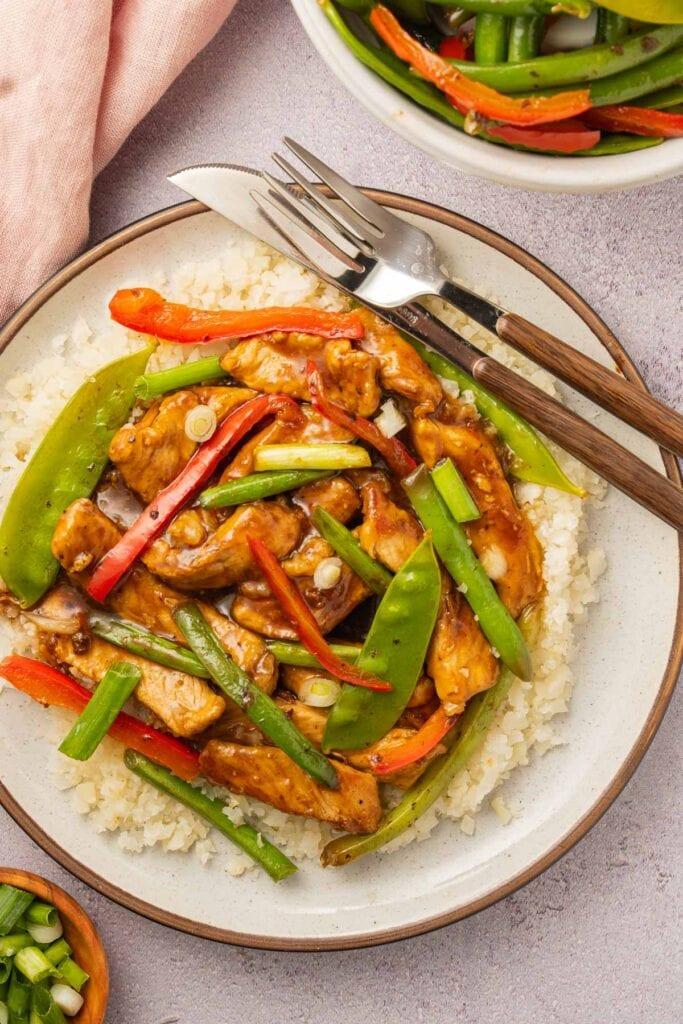 mongolian pork, pepper strips, string beans, cauliflower rice on beige plate, bowl of stir fry vegetables and chopped scallions