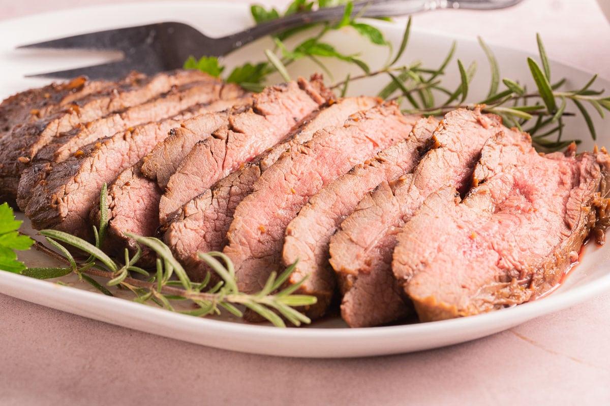 sliced steak on white platter with herbs.
