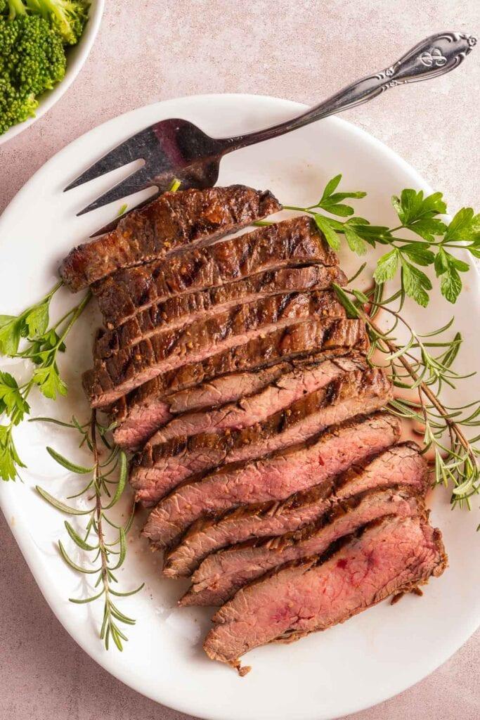 sliced steak on white platter with herbs and fork.